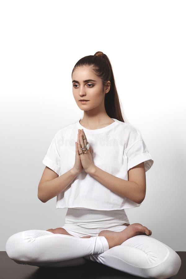 Bella giovane donna nell'yoga che posa su un fondo dello studio Forme perfette, misura e forte ente fotografia stock