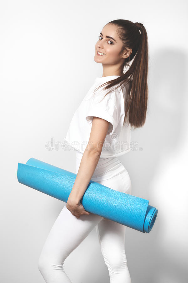 Bella giovane donna nell'yoga che posa su un fondo dello studio Forme perfette, misura e forte ente immagine stock libera da diritti