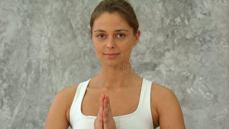Bella giovane donna nell'yoga di pratica degli abiti sportivi ed esaminare macchina fotografica mentre sedendosi nella posizione  immagine stock
