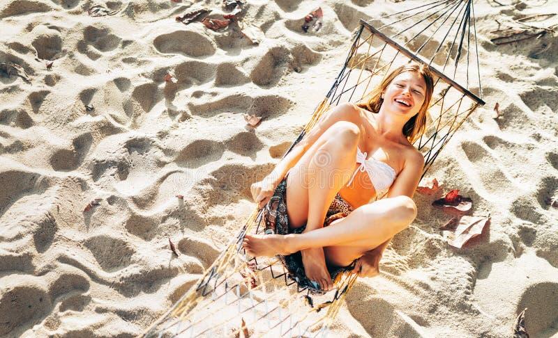 Bella giovane donna nella cima di bikini che oscilla in amaca sulla spiaggia sabbiosa e allegra ridendo in camera vista superiore fotografia stock libera da diritti