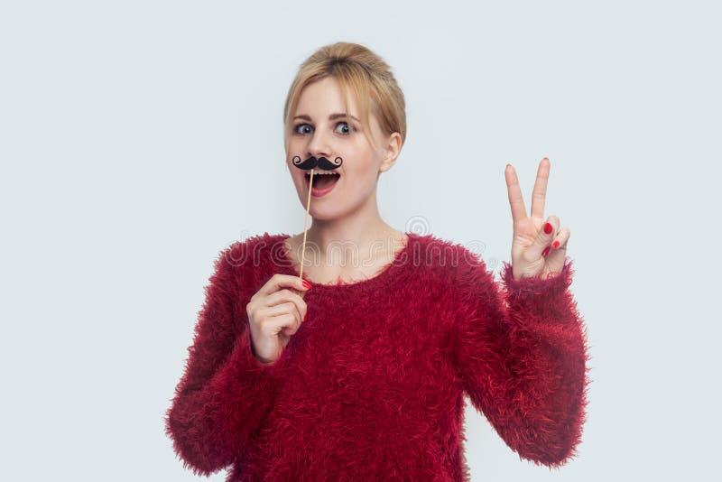 Bella giovane donna nella condizione rossa della blusa, tenendo l'autoadesivo antropoide dei baffi, mostrante il segno di pace co immagini stock libere da diritti