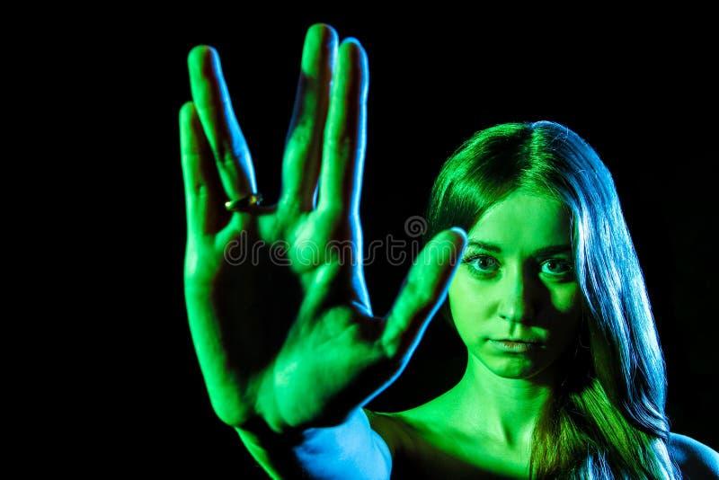 Bella giovane donna nella luce verde che mostra il segno straniero immagini stock