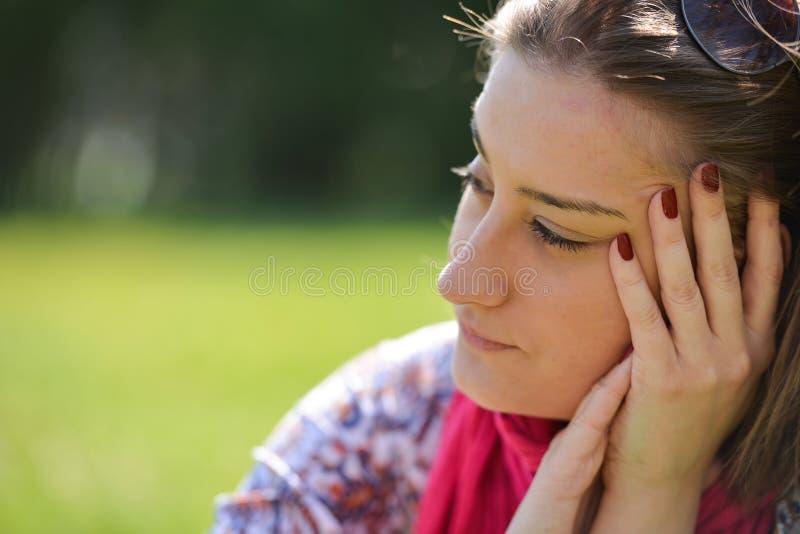 Bella giovane donna premurosa nel parco su un'estate calda da fotografie stock