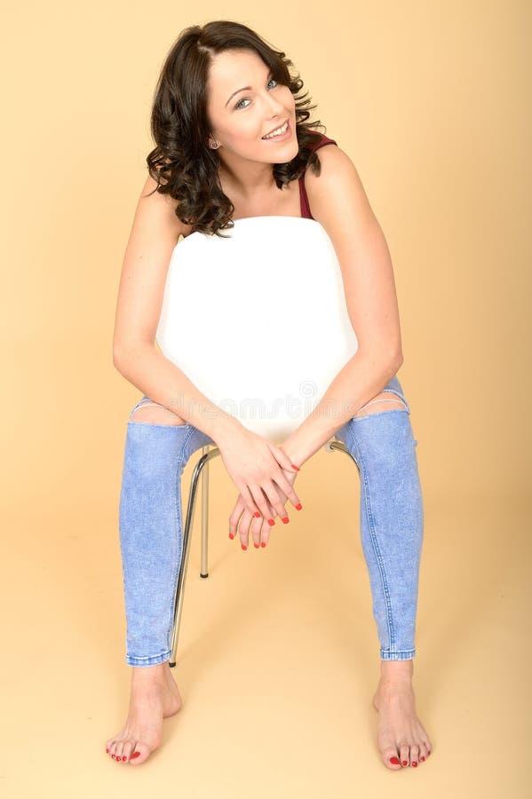 Bella giovane donna rilassata allegra felice che si siede in una sedia bianca fotografia stock libera da diritti