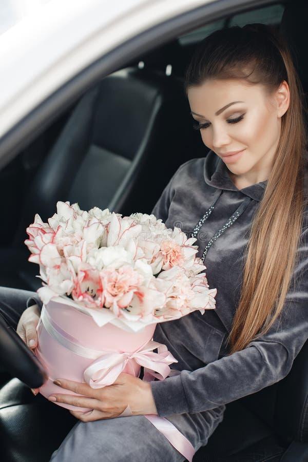 Bella giovane donna, sedentesi sul sedile dell'autista in un'automobile con una scatola rosa in pieno di tenero, bianco, con un b fotografia stock