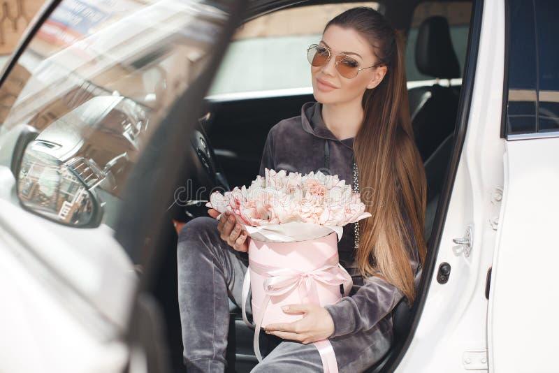 Bella giovane donna, sedentesi sul sedile dell'autista in un'automobile con una scatola rosa in pieno di tenero, bianco, con un b fotografie stock