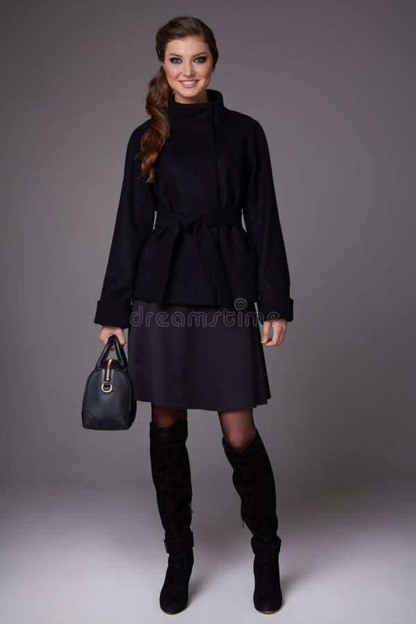 Bella giovane donna sexy di affari con trucco di sera che porta una gonna scura hee del cappotto della lana del ginocchio all'alt fotografia stock