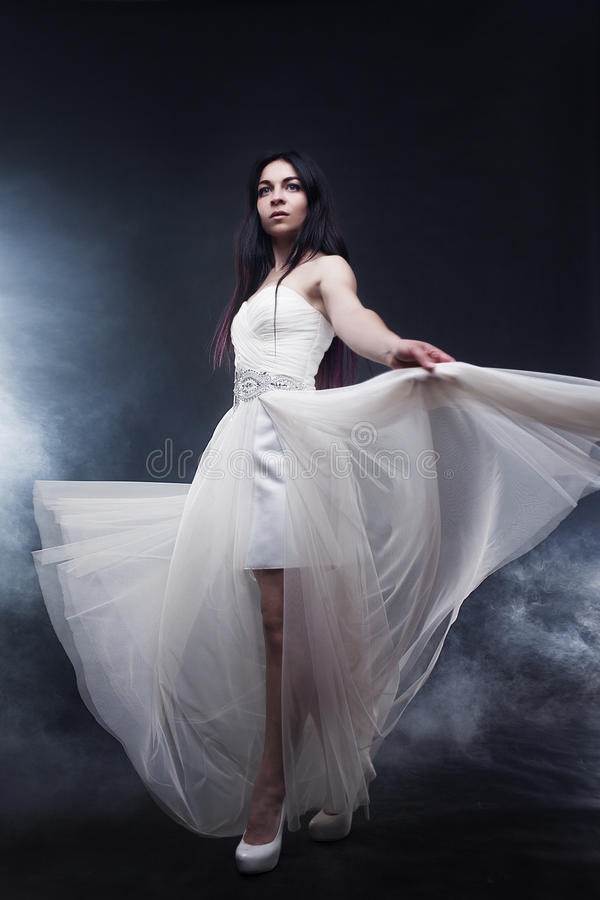 Bella giovane donna sexy Ritratto della ragazza in vestito bianco lungo, stile mistico e misterioso, fondo scuro fotografia stock