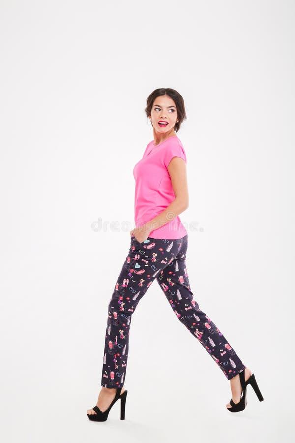 Bella giovane donna sicura che cammina e che guarda indietro fotografia stock libera da diritti