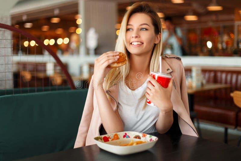 Bella giovane donna soddisfatta con un sorriso che mangia un hamburger fotografia stock libera da diritti