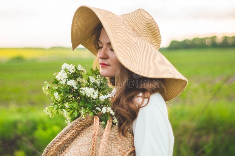 Bella giovane donna sorridente in cappello d'annata di paglia e del vestito nei wildflowers del campo La ragazza sta tenendo un c immagini stock