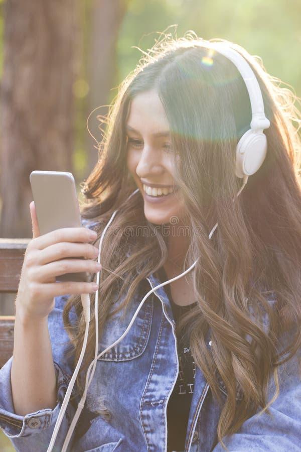 Bella giovane donna sorridente che ascolta la musica e che tiene di mattina fotografia stock libera da diritti