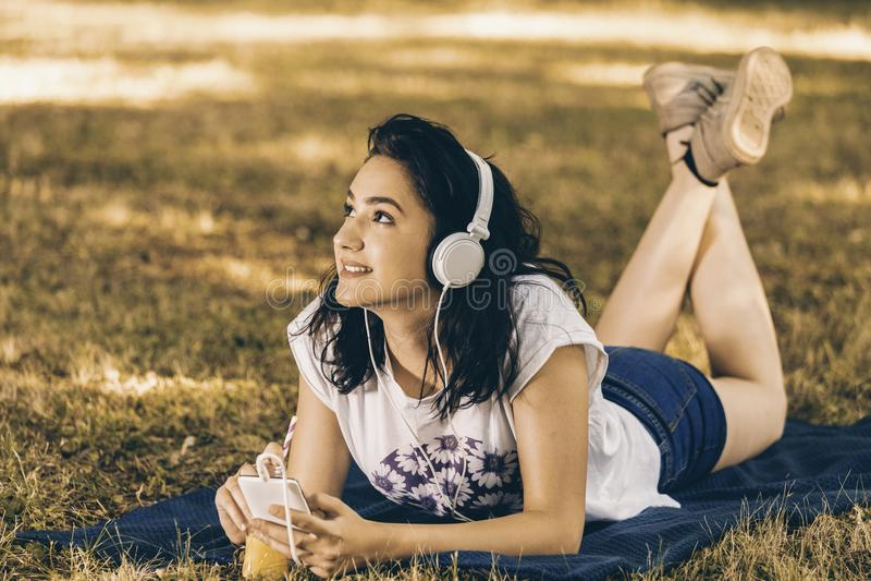 Bella giovane donna sorridente che ascolta la musica e che tiene di mattina immagini stock libere da diritti