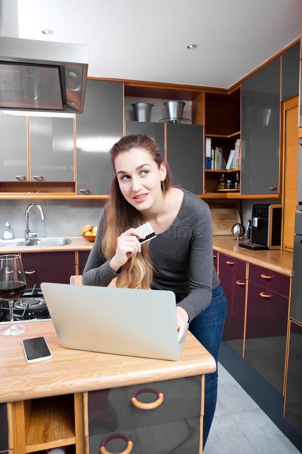 Bella giovane donna sorridente che compera online per il commercio mobile immagini stock libere da diritti