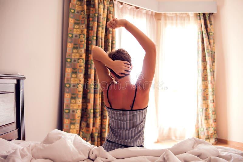 Bella giovane donna sorridente che si siede sul letto e che allunga di mattina alla camera da letto fotografia stock libera da diritti
