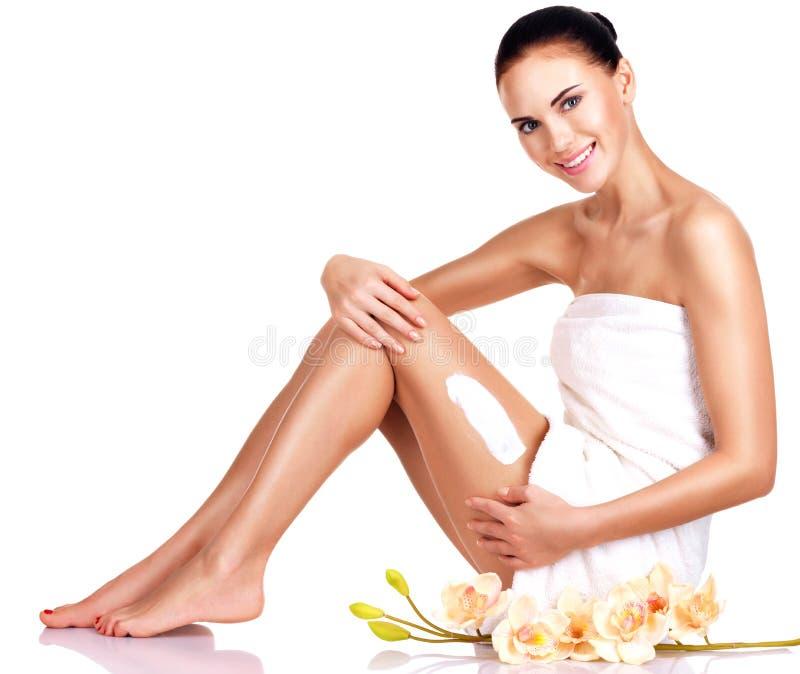 Bella giovane donna sorridente che usando crema. fotografia stock