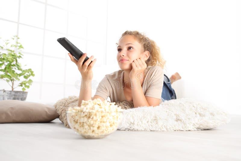 Bella giovane donna sorridente con il Th di sorveglianza del telecomando della TV fotografie stock libere da diritti