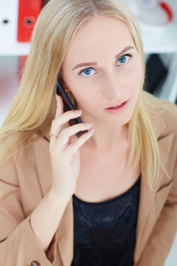 Bella giovane donna sorridente del primo piano che parla sul telefono cellulare nell'ufficio immagine stock libera da diritti