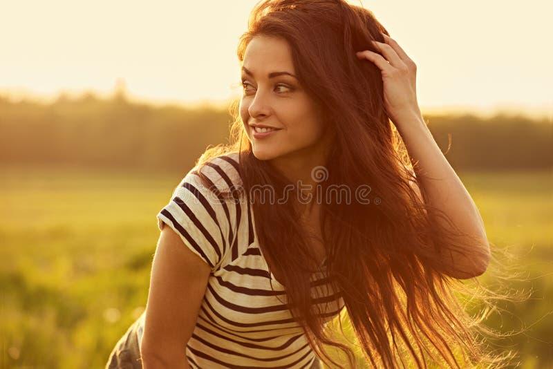 Bella giovane donna sorridente di pensiero che sembra soddisfatta di capelli luminosi lunghi sul fondo di estate di tramonto dell immagini stock