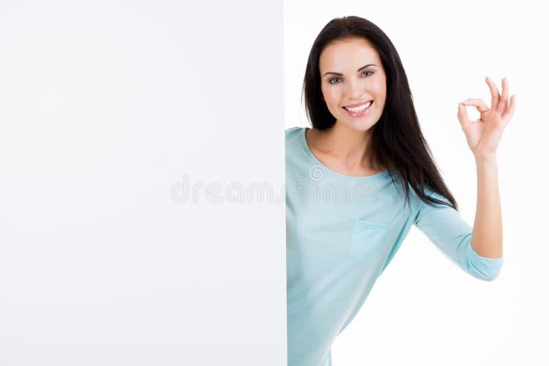 Bella giovane donna sorridente felice che mostra insegna in bianco fotografia stock