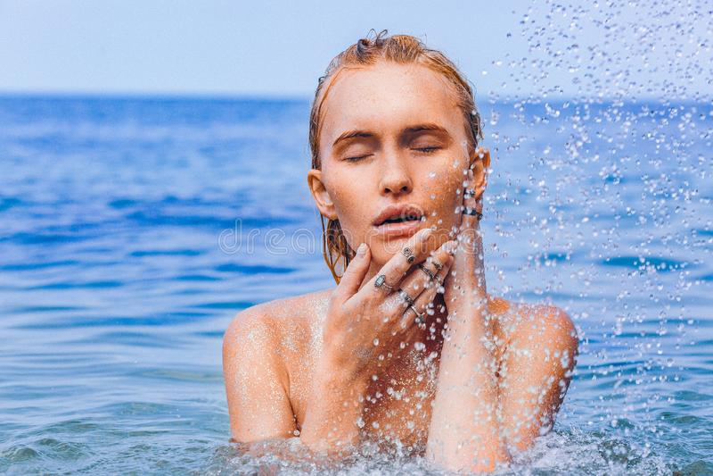 Bella giovane donna in spruzzata della fine dell'acqua sul ritratto sensuale fotografie stock