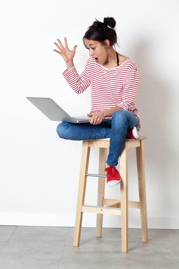Bella giovane donna stupita che comunica con la sorpresa al suo computer fotografie stock libere da diritti