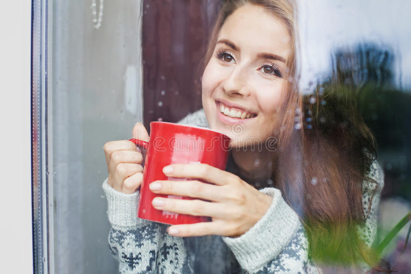 Bella giovane donna su una mattina enjoing del balcone con la tazza di caffè fotografie stock libere da diritti