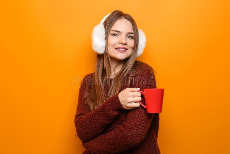 Bella giovane donna in tazza calda della tenuta del maglione di tè caldo sul fondo di colore immagine stock