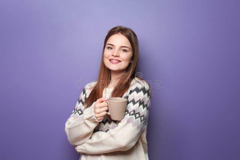 Bella giovane donna in tazza calda della tenuta del maglione di tè caldo sul fondo di colore immagini stock