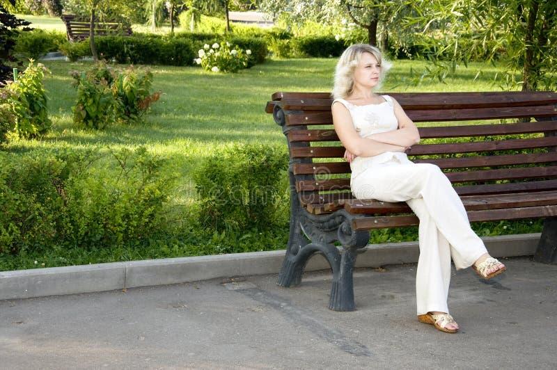 Bella giovane donna triste che si siede sul banco fotografia stock