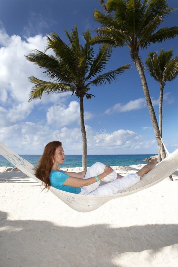 Bella giovane donna in un'amaca sulla spiaggia su fondo delle palme e del mare fotografia stock libera da diritti