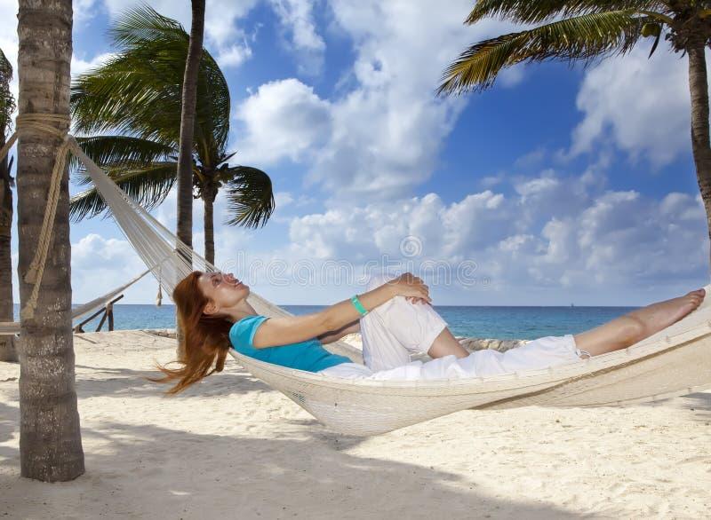 Bella giovane donna in un'amaca sulla spiaggia su fondo delle palme e del mare fotografie stock