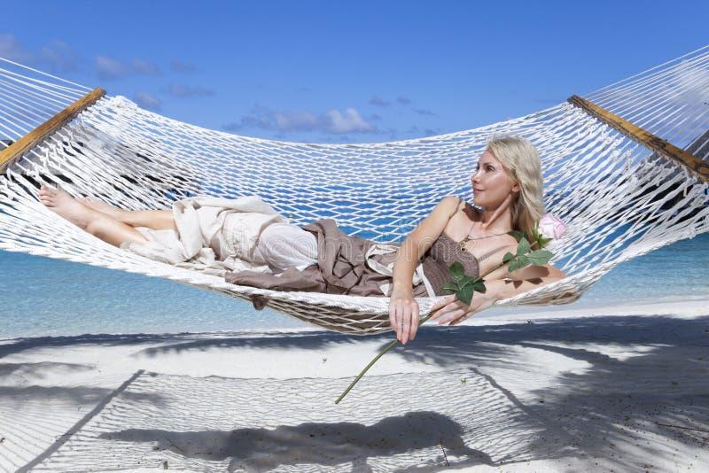 Bella giovane donna in un'amaca sulla spiaggia su fondo delle palme e del mare immagini stock