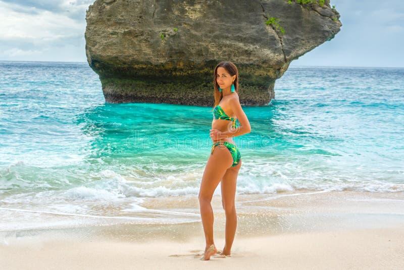 Bella giovane donna in un bikini del turchese che posa sulla spiaggia sui precedenti delle rocce Fine in su immagine stock libera da diritti