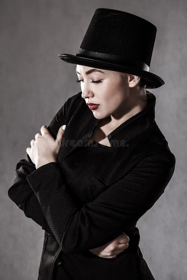 bella giovane donna in un black hat fotografie stock