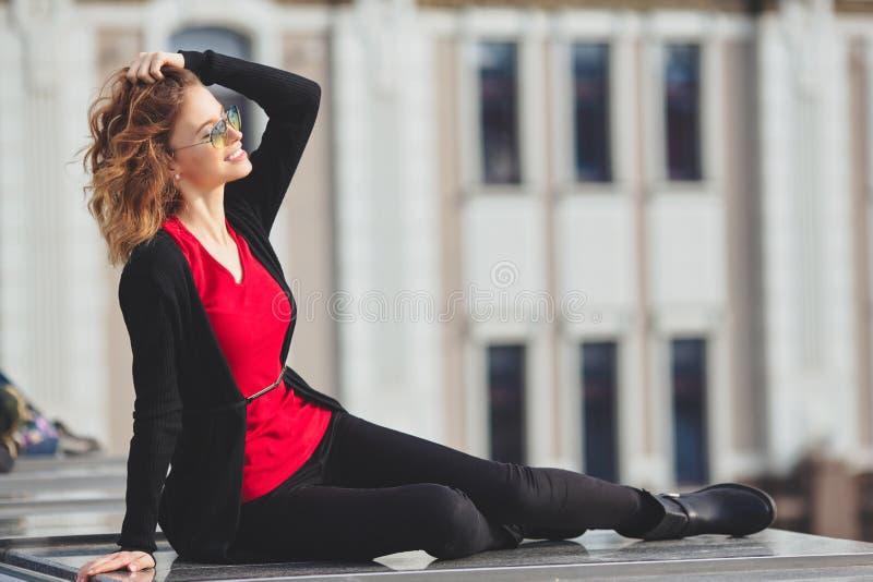 Bella giovane donna in un bomber nero che si siede sul ponte immagine stock libera da diritti