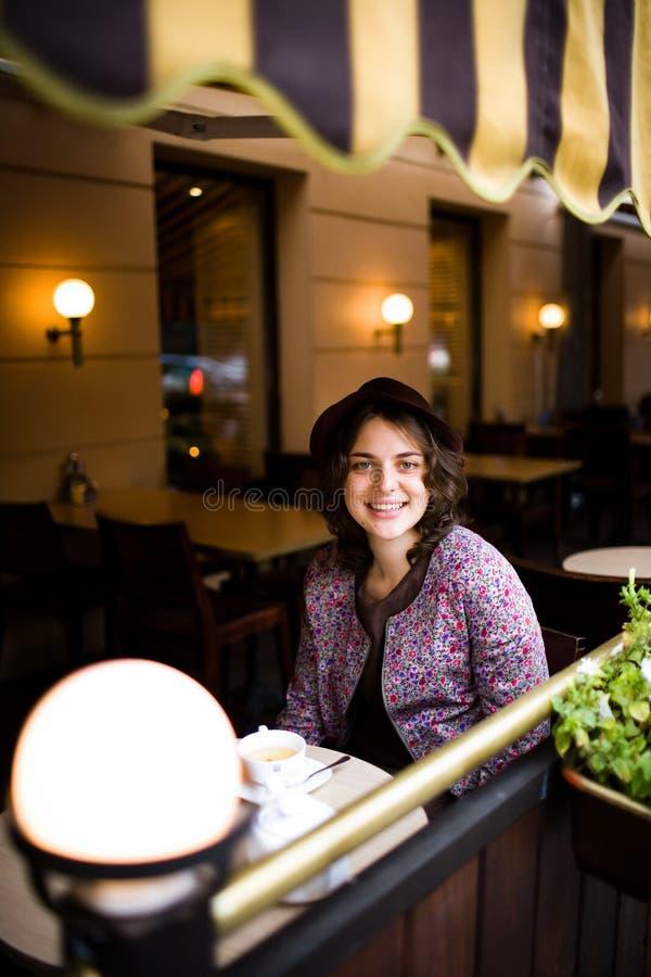 Bella giovane donna in un cappello con una tazza di tè che si siede in un caffè che esamina la macchina fotografica e sorridere immagini stock