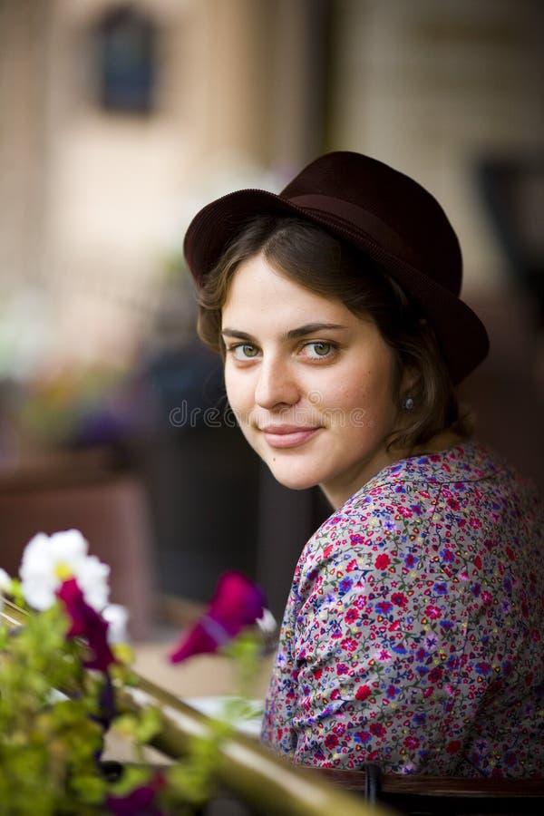 Bella giovane donna in un cappello con una tazza di tè che si siede in un caffè che esamina la macchina fotografica e sorridere immagini stock libere da diritti