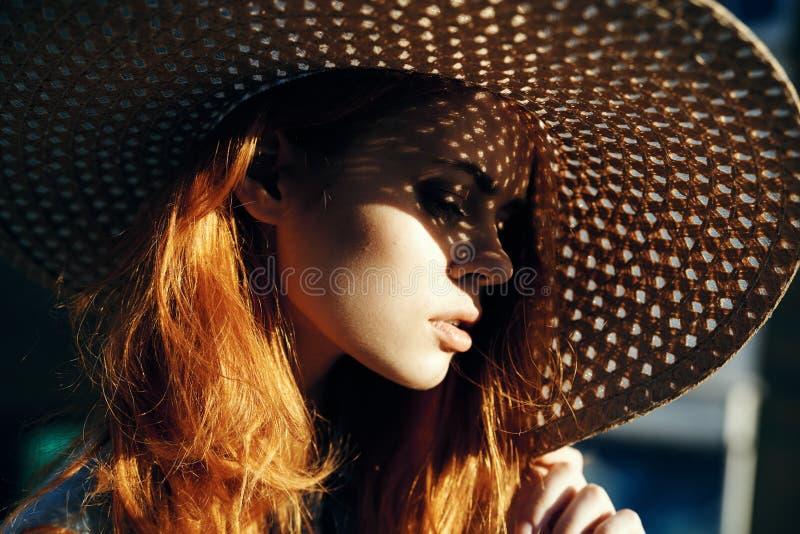 Bella giovane donna in un cappello di vimini, ritratto, sole, estate immagine stock