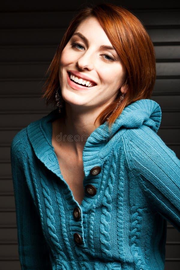 Bella giovane donna in un maglione blu immagine stock