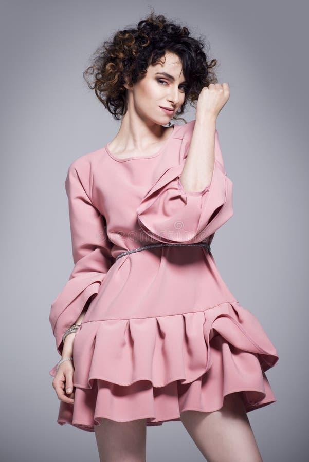 Bella giovane donna in un vestito rosa con gli arricciamenti immagine stock