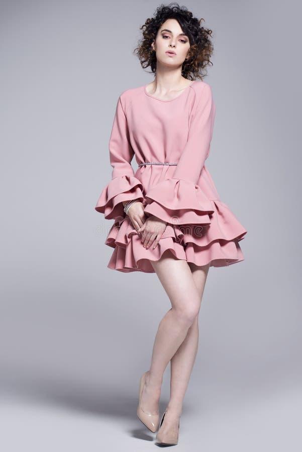 Bella giovane donna in un vestito rosa con gli arricciamenti fotografia stock