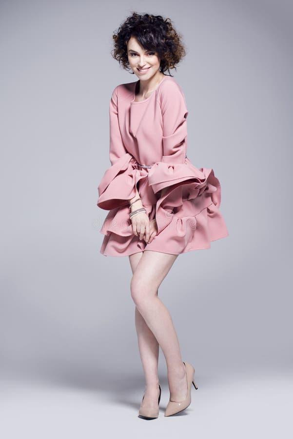 Bella giovane donna in un vestito rosa con gli arricciamenti fotografia stock libera da diritti