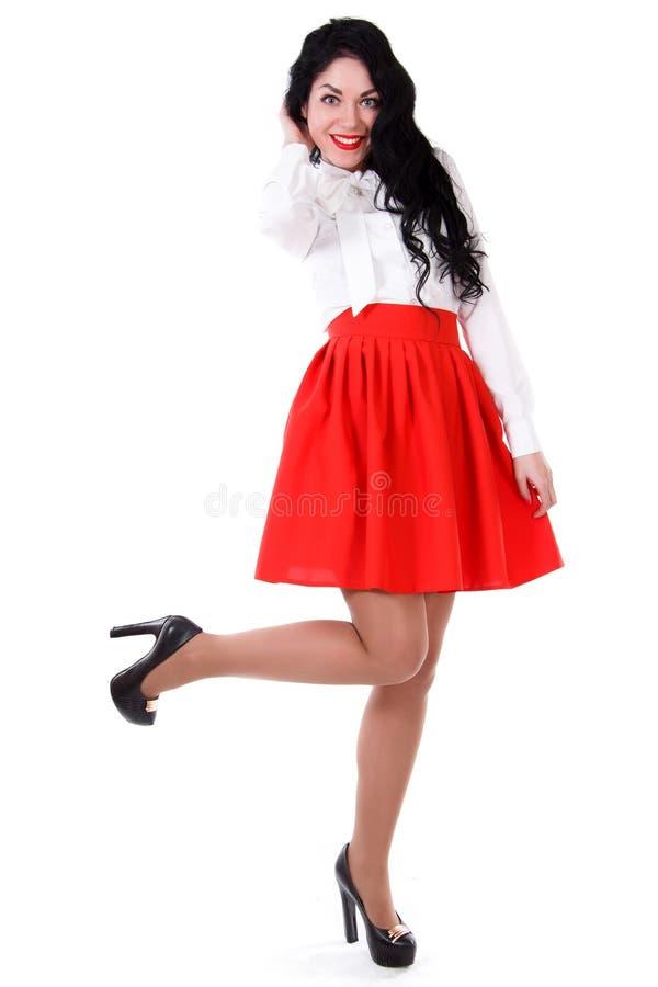 Bella giovane donna in una blusa bianca ed in una gonna rossa immagine stock