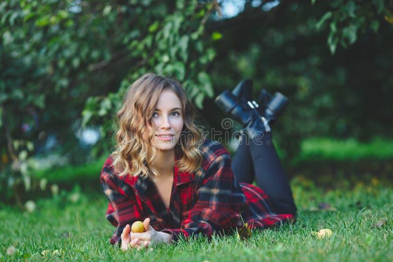 Bella giovane donna in una camicia maschio della flanella che si trova sull'erba verde fotografia stock libera da diritti