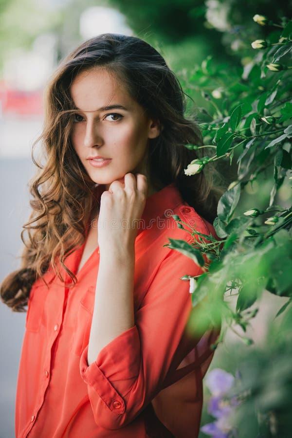 Bella giovane donna in una gonna rossa che sta fra le rose immagini stock libere da diritti