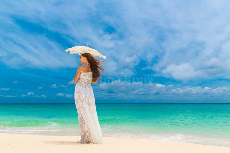 Bella giovane donna in vestito bianco con l'ombrello su un tropicale immagini stock