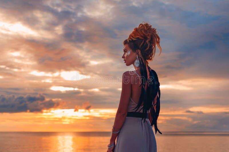 Bella giovane donna in vestito elegante sulla spiaggia al tramonto immagine stock