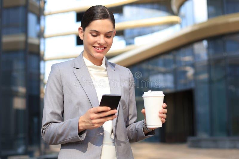 Bella giovane donna in vestito facendo uso dello Smart Phone e del sorridere mentre stando all'aperto immagine stock