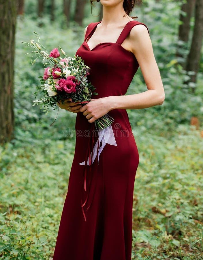 Bella giovane donna in vestito lungo da Borgogna con il mazzo fotografia stock